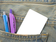 Tarjeta en un bolsillo trasero de vaqueros del dril de algodón como fondo Imágenes de archivo libres de regalías