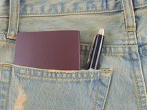 Tarjeta en un bolsillo trasero de vaqueros del dril de algodón como fondo Foto de archivo libre de regalías