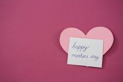 Tarjeta feliz del día de la madre con forma del corazón contra fondo rosado Imagenes de archivo