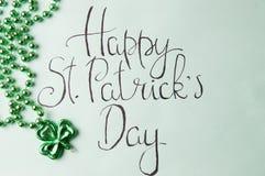 Tarjeta feliz del día de St Patrick y accesorios verdes Imágenes de archivo libres de regalías