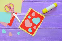 Tarjeta linda del día de tarjetas del día de San Valentín hecha del papel coloreado Scissirs, palillo del pegamento, papel colore Foto de archivo
