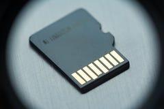 Tarjeta micro negra del sd con los contactos del oro en una superficie metálica gris imagen de archivo libre de regalías