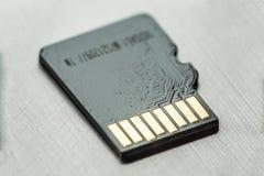 Tarjeta micro negra del sd con los contactos del oro en una superficie metálica gris imágenes de archivo libres de regalías