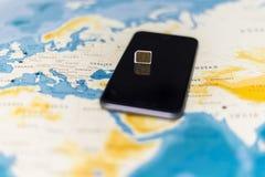 Tarjeta micro y smartphone de SIM en el mapa del mundo imagenes de archivo