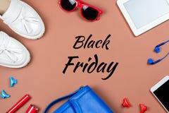 Tarjeta negra de viernes con los artículos de la ropa y de los accesorios femeninos en fondo marrón Foto de archivo libre de regalías