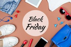 Tarjeta negra de viernes con los artículos de la ropa y de los accesorios femeninos en fondo marrón Fotografía de archivo libre de regalías