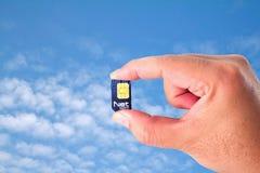 Tarjeta neta de Sim en una mano en el cielo azul Foto de archivo libre de regalías