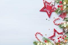 Tarjeta o bandera del día de fiesta de la Feliz Navidad con las ramas nevosas del abeto, las estrellas rojas y las decoraciones f imagen de archivo libre de regalías