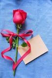 Tarjeta roja de la rosa y de papel en el fondo azul de la mezclilla para Valentine& x27; concepto del fondo de s imágenes de archivo libres de regalías