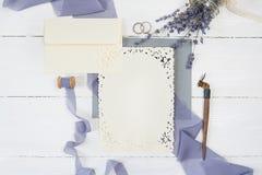 Tarjeta, sobre y cinta en blanco de felicitación con dos anillos de bodas con las flores de la lavanda y la pluma caligráfica con foto de archivo