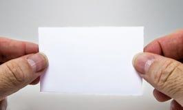 Tarjeta vacía blanca con una mano del hombre, gratis texto, en un fondo gris Fotos de archivo libres de regalías
