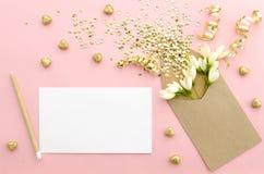 Tarjeta vacía con el sobre, las lentejuelas del brillo, el confeti, los corazones y las flores en un backgroundgold suavemente ro imagenes de archivo
