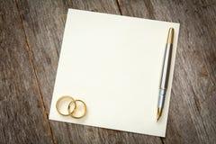 Tarjeta vacía con los anillos de oro Fotos de archivo