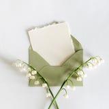 Tarjeta vacía de la cartulina con flores y un sobre Fotos de archivo libres de regalías