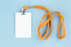 Tarjeta vacía/icono de la identificación con una correa anaranjada, en un fondo azul Fotos de archivo libres de regalías