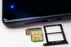 Tarjeta y bandeja de SIM para ellos al lado del teléfono Foto de archivo libre de regalías