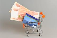 Tarjeta y dinero de crédito dentro del carro de la compra en gris Fotografía de archivo libre de regalías