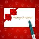 Tarjeta y pluma de la Feliz Navidad en fondo del copo de nieve Foto de archivo