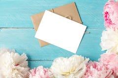 Tarjeta y sobre en blanco de felicitación con el ramo de las flores de la peonía en fondo de madera azul Endecha plana Mofa para  imagen de archivo libre de regalías
