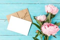 Tarjeta y sobre en blanco de felicitación con el ramo de las flores de la peonía en fondo de madera azul Endecha plana Mofa para  imagenes de archivo
