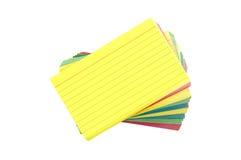 Tarjetas de índice en blanco coloridas avivadas hacia fuera aisladas en blanco Fotos de archivo libres de regalías