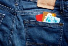 Tarjetas de crédito coloridas en un bolsillo azul de la parte posterior de la mezclilla foto de archivo