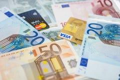 Tarjetas de crédito de la visa y de Mastercard en billetes de banco euro Fotos de archivo
