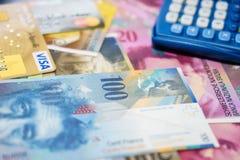 Tarjetas de crédito de la visa y de Mastercard en billetes de banco suizos Imagenes de archivo