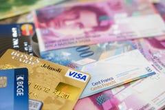 Tarjetas de crédito de la visa y de Mastercard en billetes de banco suizos Fotos de archivo libres de regalías
