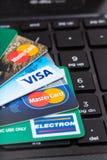 Tarjetas de crédito en el teclado de ordenador negro Imágenes de archivo libres de regalías
