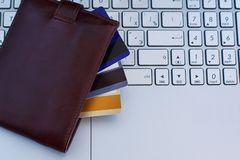 Tarjetas de crédito en la cartera en el teclado del ordenador portátil fotos de archivo libres de regalías
