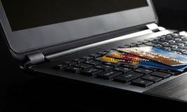 Tarjetas de crédito en un ordenador portátil Fotos de archivo