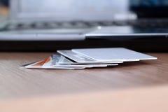 Tarjetas de crédito en una tabla y un ordenador portátil detrás Imágenes de archivo libres de regalías