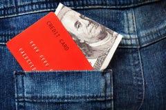 Tarjetas de crédito y nota rojas del dólar en el bolsillo de los vaqueros Fotografía de archivo libre de regalías