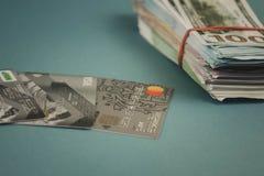 Tarjetas de crédito y un paquete de dinero en un fondo azul llano fotografía de archivo libre de regalías
