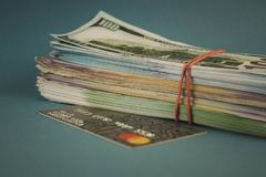Tarjetas de crédito y un paquete de dinero en un fondo azul llano imagenes de archivo