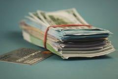 Tarjetas de crédito y un paquete de dinero en un fondo azul llano foto de archivo libre de regalías
