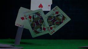 Tarjetas de juego que caen abajo en la tabla verde metrajes