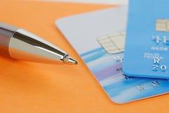 Tarjetas de la pluma y de crédito en un cuaderno de notas anaranjado Fotos de archivo