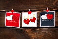 Tarjetas de las tarjetas del día de San Valentín que cuelgan en fondo de madera Imágenes de archivo libres de regalías