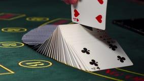 Tarjetas de mezcla del crupié, demostraciones una en la tabla verde en el casino almacen de video