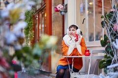 Tarjetas de Navidad alegres de la escritura de la muchacha en café Imagen de archivo libre de regalías