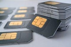 Tarjetas de SIM para los teléfonos móviles en una pila que se inclina contra la pila Imagen de archivo