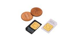 Tarjetas de SIM para los teléfonos móviles y las monedas Imagen de archivo