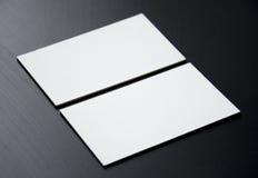 Tarjetas de visita blancas en blanco en un fondo negro Imagenes de archivo
