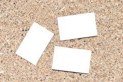 Tarjetas de visita en blanco blancas en la arena de la playa Imagen de archivo libre de regalías