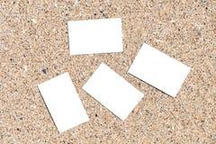 Tarjetas de visita en blanco blancas en la arena de la playa Foto de archivo
