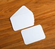 Tarjetas de visita en blanco con las esquinas redondeadas en un fondo de madera Imagen de archivo libre de regalías