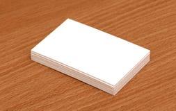 Tarjetas de visita en blanco empiladas para arriba en un escritorio Fotos de archivo libres de regalías