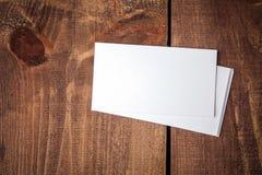 Tarjetas de visita en blanco en la tabla de madera fotos de archivo